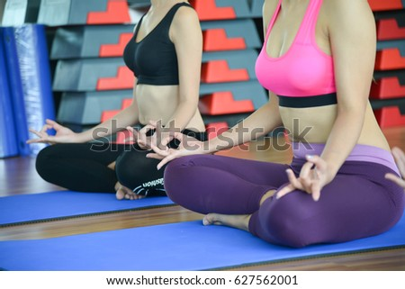 young women torso in yoga class making exercises. Unrecognizable girls do meditation pose for relaxation. Healthy lifestyle in fitness club. #627562001