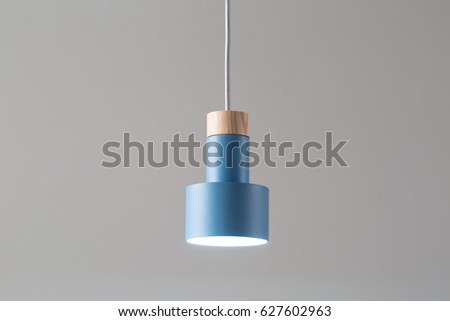 Glowing metal blue lamp with light wooden part is hanging on the white cable on the gray background. Closeup photo. Horizontal. #627602963