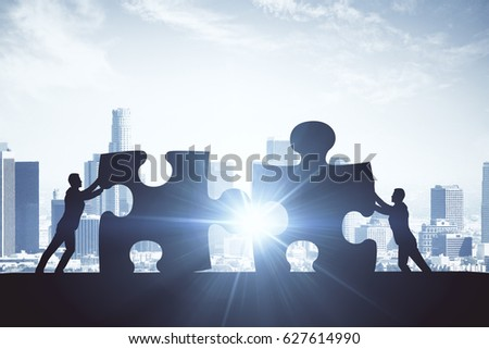 People silhouettes putting puzzle pieces together on city background with sunlight. Teamwork concept #627614990