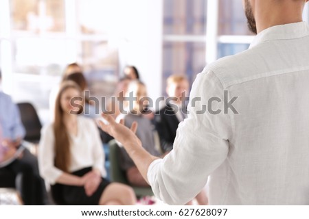 Business trainer giving presentation to group of people Royalty-Free Stock Photo #627628097