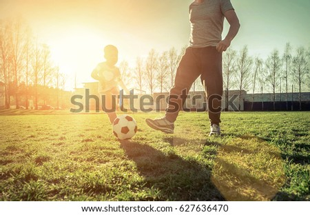 Father and son playing together with ball in football under sun light. Green field in city park at sunny day. #627636470