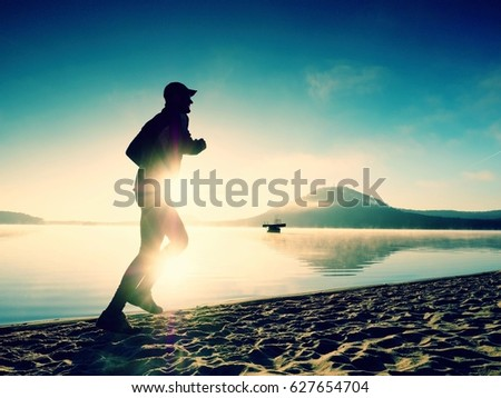 Silhouette of sport active man running on the lake beach at sunrise. Healthy lifestyle. Alone young fitness man exercise  at morning beach #627654704