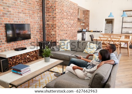Couple Sit On Sofa In Open Plan Lounge Watching Television #627662963