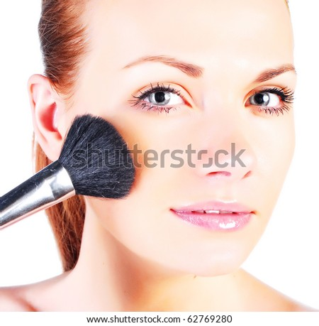 Portrait of attractive young adult woman applying blusher #62769280