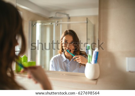 Portrait of a beautiful woman brushing teeth and looking in the mirror in the bathroom. Royalty-Free Stock Photo #627698564