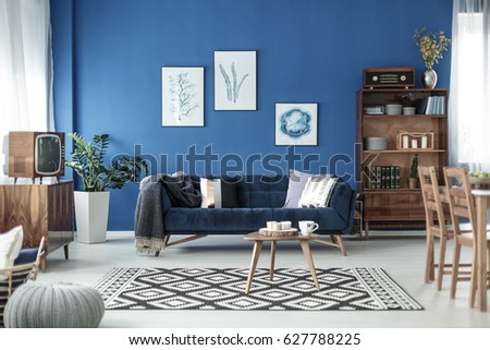 Retro style cozy living room with blue walls and white floor