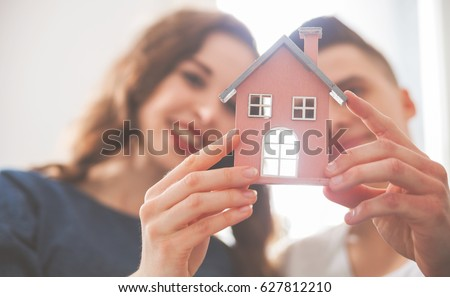 Young loving couple with small wooden house new home concept Royalty-Free Stock Photo #627812210