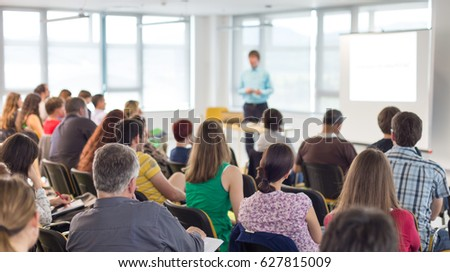 Business and entrepreneurship symposium. Speaker giving a talk at business meeting. Audience in conference hall. Rear view of unrecognized participant in audience. #627815009