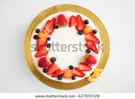 Cake with whipped cream, fresh strawberries, blueberries and physalis. Top view. Picture for a menu or a confectionery catalog.