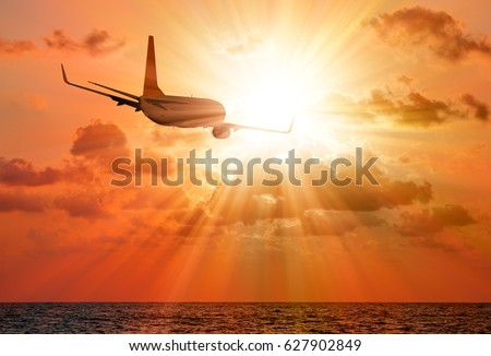 Airplane flying above tropical sea at sunset #627902849