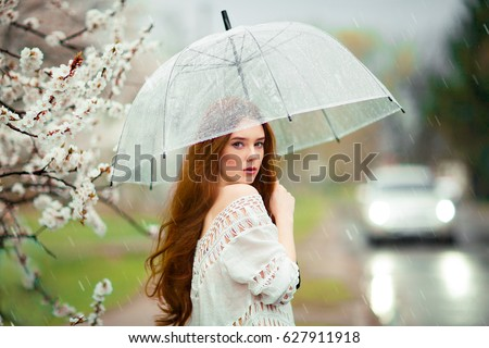 Spring Beautiful romantic red haired girl in white lace dress and jeans standing near blooming tree with transparent umbrella.Young model near road under rain looking at camera. #627911918