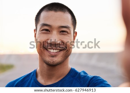 Portrait of a smiling athletic young Asian man in sportswear taking a selfie while out for an early morning run