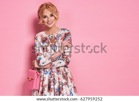 Fashion photo of a beautiful elegant young woman in a pretty dress with flowers holding handbag posing over pink background. Fashion spring summer photo #627959252