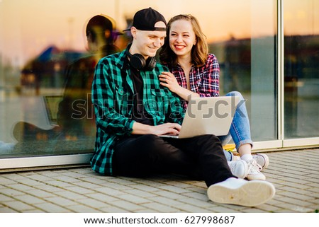 Young hipster couple using a laptop and sitting on pavement outdoor. #627998687