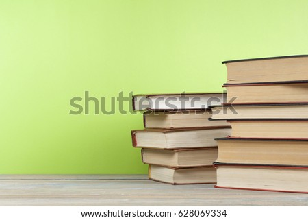 Stack of books on wooden table on green wall background. Copy space for text. Back to school. Education concept. #628069334