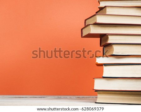 Stack of books on wooden table on red wall background. Copy space for text.Back to school. #628069379