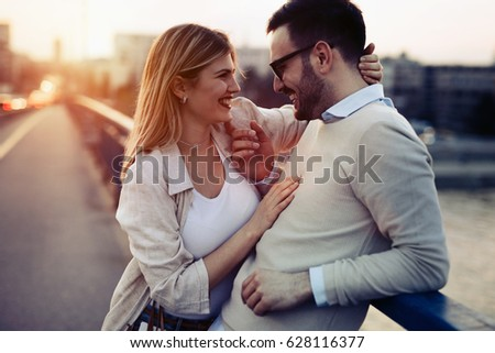 Beautiful cheerful couple in love  dating and smiling outdoors #628116377