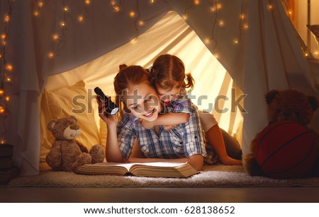 reading and family games in children's tent. mother and child daughter with  book and flashlight before going to bed #628138652