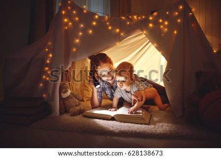 reading and family games in children's tent. mother and baby son with  book and flashlight before going to bed