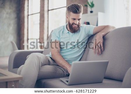 Young bearded man is making shopping online sitting at home on the cozy sofa #628171229