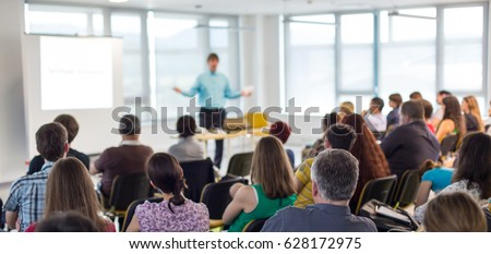 Business and entrepreneurship symposium. Speaker giving a talk at business meeting. Audience in conference hall. Rear view of unrecognized participant in audience. #628172975