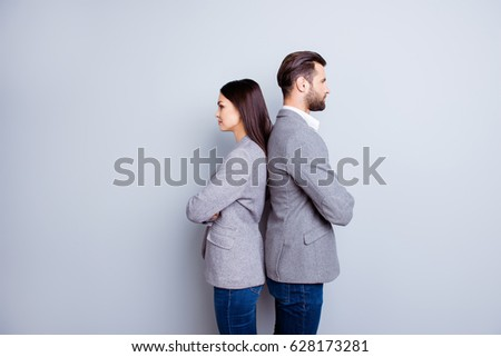 Two professionals in business and finance in gray jackets and jeans standing back-to-back on gray backdrop #628173281