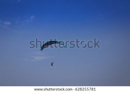 Burgas - July 29: Oil green paraglider flying against the blue sky with white clouds on July 29, 2016, Burgas, Bulgaria #628255781