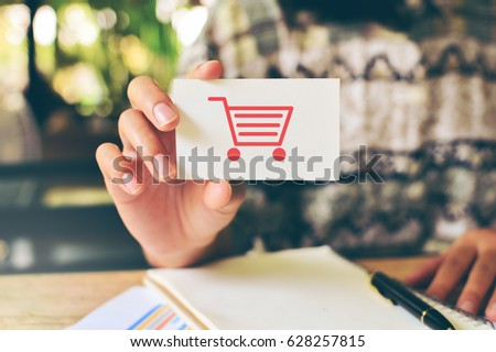 Closeup on a businesswoman holding a card with a shopping cart. #628257815