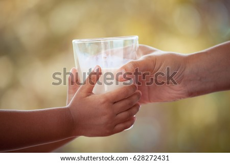 Woman hand giving glass of milk to child in vintage color tone #628272431