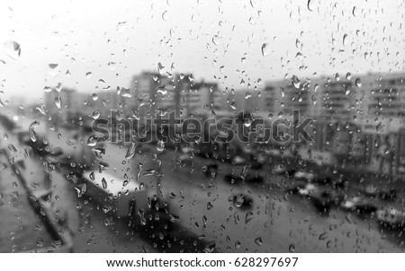 Rain on the window, rain on the window, outside the city window, in the city rain. Black and white picture of the rain