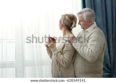 Cute elderly couple near window at home #628349141