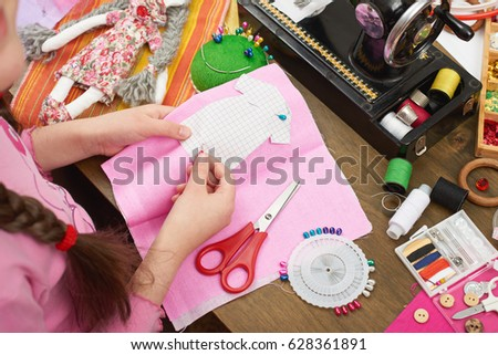 girl sews doll clothes, top view, sewing accessories top view, seamstress workplace, many object for needlework, handmade and handicraft #628361891