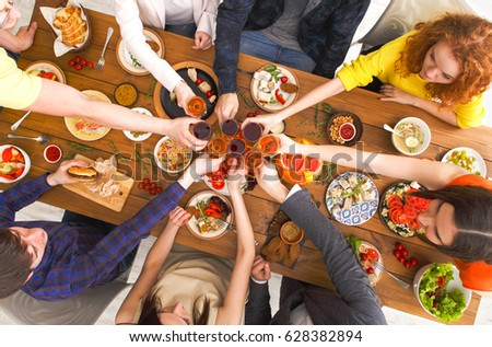 People clink glasses, saying cheers, eat healthy meals at party dinner table. Friends celebrate with organic food, ratatoille and corn barbecue on wooden table top view. #628382894