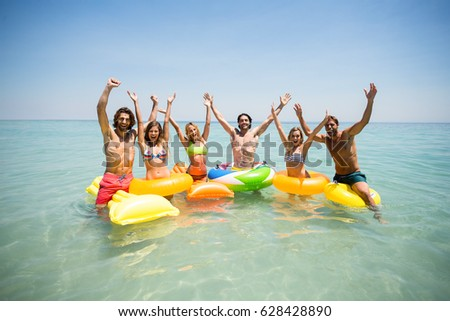 Portrait of cheerful friends enjoying on inflatable rings and pool rafts in sea against sky #628428890