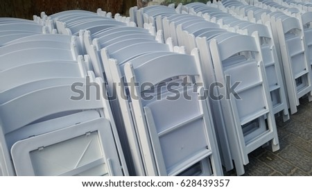 Dozens of fold up white plastic chairs stacked #628439357