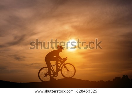 Silhouette of young man riding a bicycle on the sunset #628453325