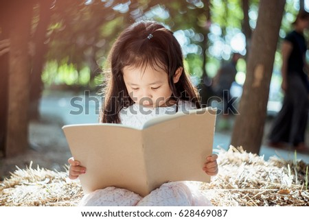 A cute child is reading a book and drawing a picture in the park.