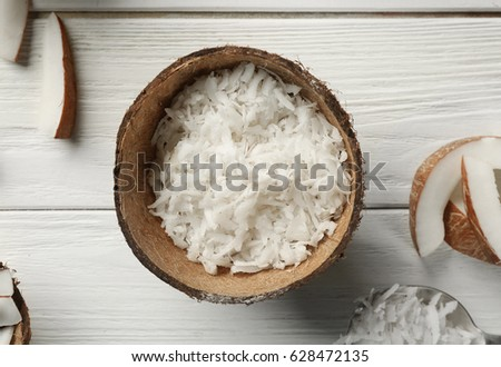 Grated coconut in shell on wooden background #628472135