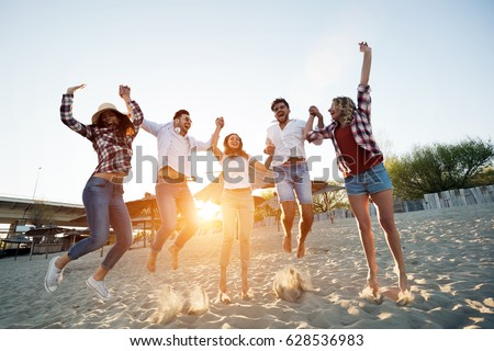 Group of happy young people enjoying summer vacation on beach #628536983