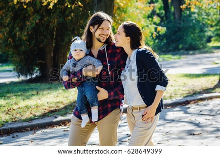 Happy family in the park. Mom, dad and baby happy walk. #628649399