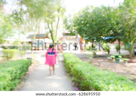 BLURRED BACKGROUND WOMAN WALKING IN PARK #628695950