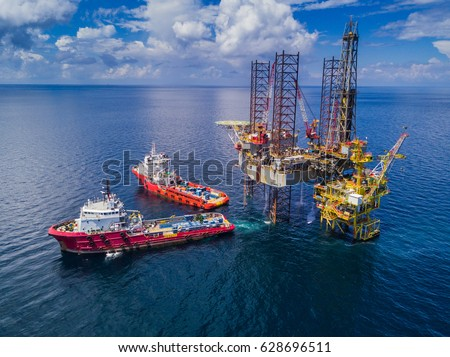 Supply Vessel Alongside Offshore Jack Up Drilling Rig Over The Production Platform in The Middle of The Sea Royalty-Free Stock Photo #628696511