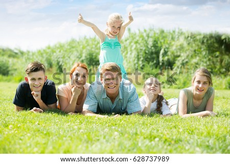 Young man and woman with four kids lying in park on summer day #628737989
