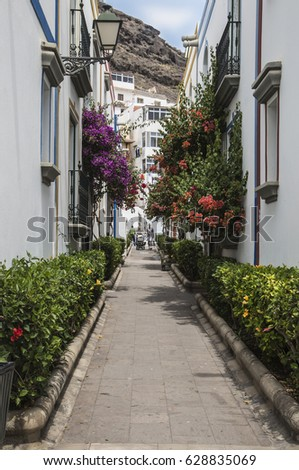 Puerto de Mogan, Gran Canaria, Canary Islands - April 11th, 2017. Sidestreet off Callejon Explanada del Castillette in Puerto de Mogan on Gran Canaria, one of the Canary Islands on a sunny Spring day. #628835069