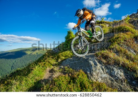A man is riding bicycle, on the background of mountains and blue sky. Beautiful summer day. Mountain bike race Royalty-Free Stock Photo #628850462
