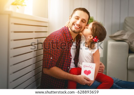 Father's day. Happy family daughter kiss dad and giving greeting card  #628893659