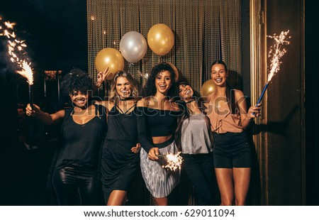 Shot of group of girls celebrating new years eve at the nightclub. Group of female friends partying in pub with sparklers. #629011094