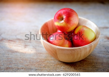Apples in wood bowl place on wooden floor. #629200565