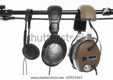 Three pairs of headphones hanging on a microphone boom stand