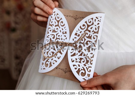 Wedding invitation card in hands in rustic style